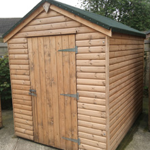 large log shed with black felt roof